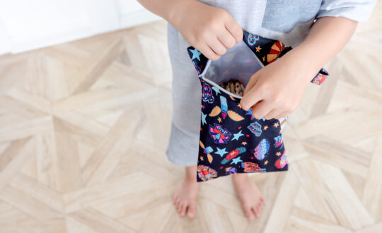 A young child holds a colourful mini wet bag contain pencils, demonstrating one of the many uses for wet bags